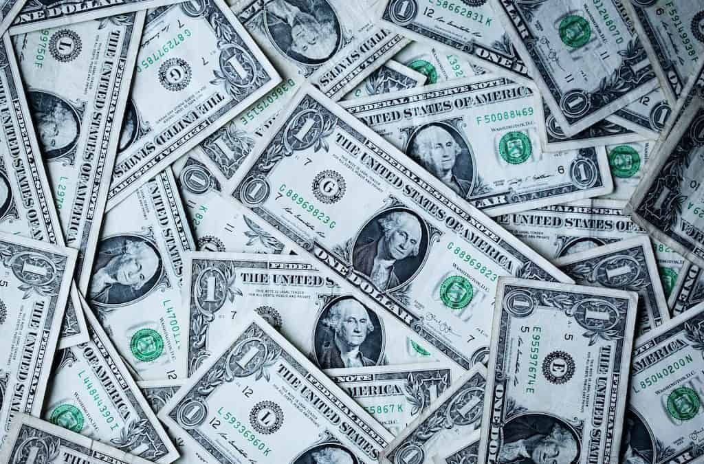 messy pile of dollar bills to get started with how to invest with $20-min