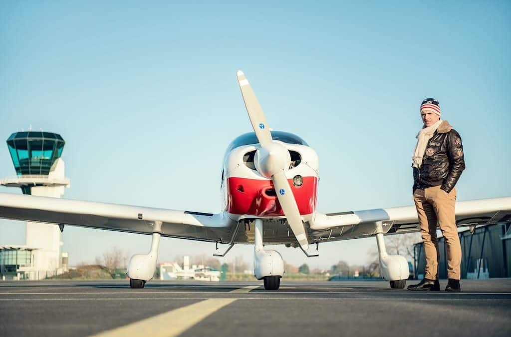man next to his private airplane as example of control your money and live better