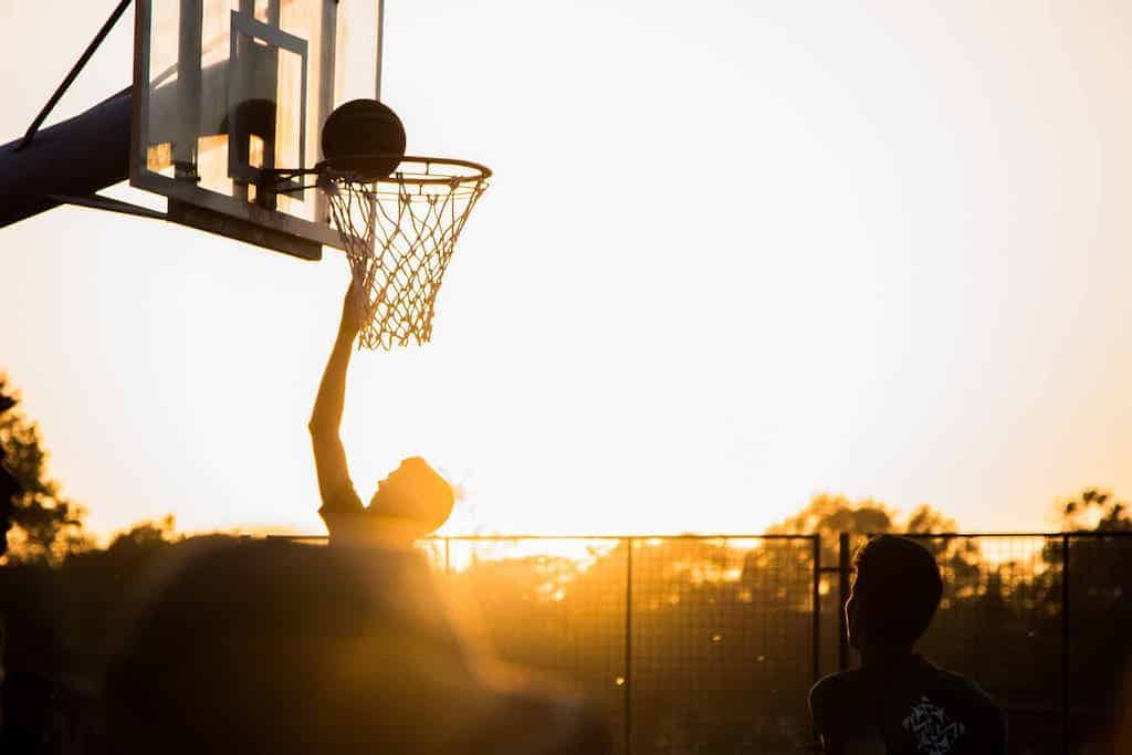man playing basketball at sunset to relieve stress and get unstuck