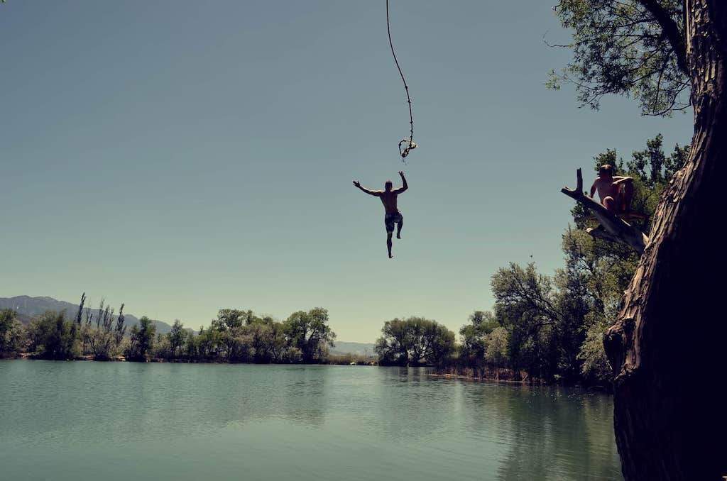 man jumping into lake from rope mastering fear getting comfortable