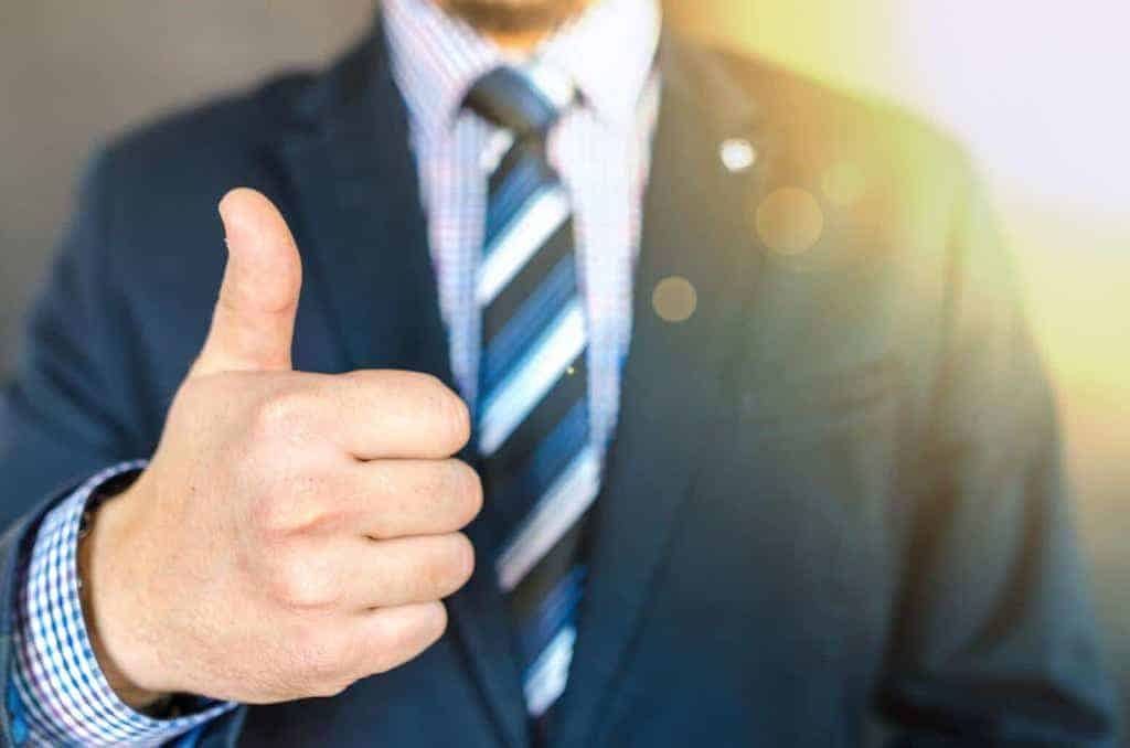 man in suit with thumbs up showing approval of success after failure-min